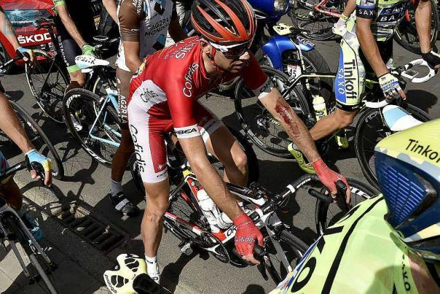 France's Nicolas Edet, injured, waits with others cyclists as the race is neutralised after a big crash at the head of the pack during the 159.5 km third stage of the 102nd edition of the Tour de France cycling race on July 6, 2015, between the belgian cities of Antwerp and Huy.  AFP PHOTO / JEFF PACHOUD